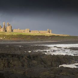DUNSTANBURGH CASTLE: Very good image and well composed in lovely light with castle holding attention and rocks plus darker sky drawing the eye to the castle
