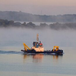 EARLY MORNING LIGHT: Very good well composed image. Dredger nicely lit and standing out against muted foreground and misty background. Nit picking-perhaps take out pylons?