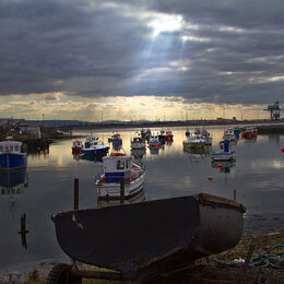 PADDY'S HOLE: Light streaming into the harbour really does set off the small boats. Eye led from foreground boat to those lit by the rays of light. Well seen, positioned and exposed. Full of interest.