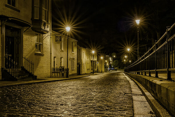 WET COBBLES: Very good street scene at night. Lights illuminating walls and fence nicely. Street lights not too overblown with effective star shapes. Nicely led into the picture and held there. Good image.