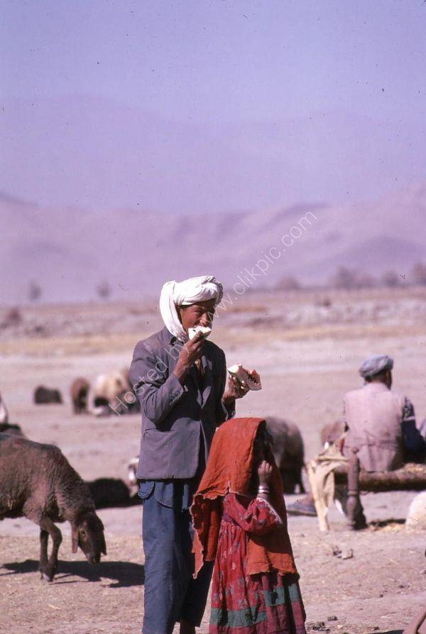 Afghani Farmer & Daughter eating Water Melon, Camel Market, Kabul