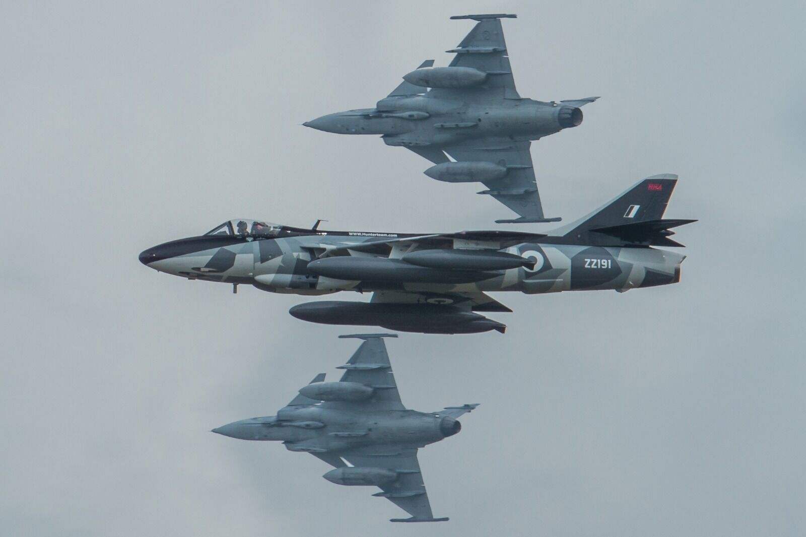Hunter Team's Hunter flies by as 2 Saab Grippen's break to land.