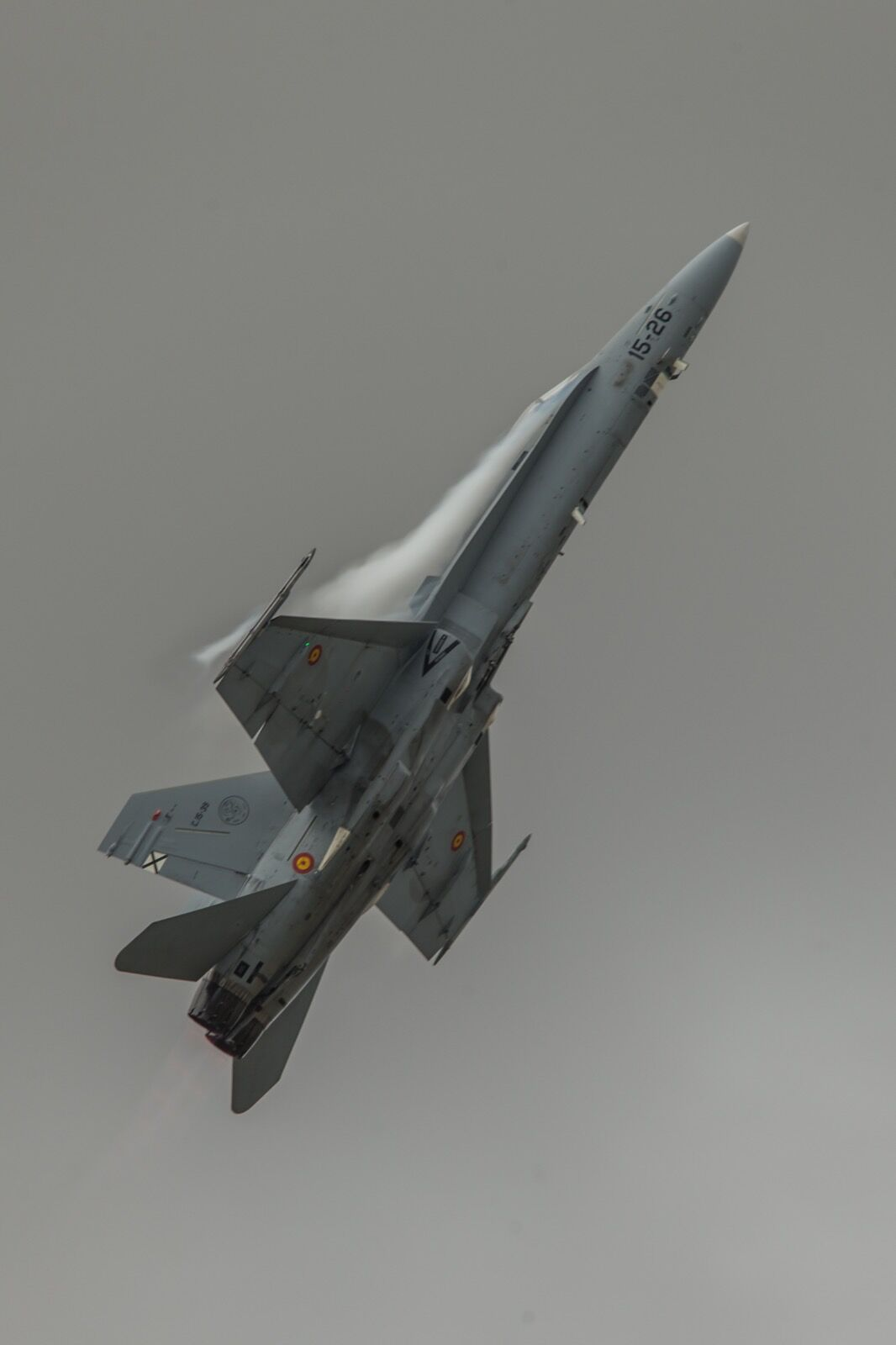 Spanish FA-18 Hornet pulls up sharply with vapour off the wings