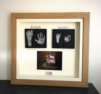 Framed, sibling 2D casts with their photo