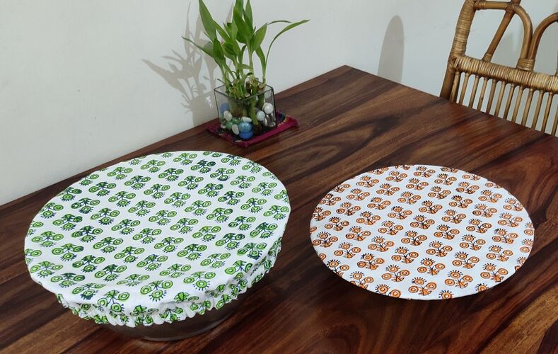 Two round bowls on a wooden table. The bowls are covered with printed, organic cotton covers. One is white with orange flower porint, the other i d ehite with green fliwer print.