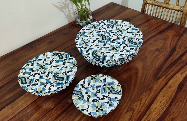Three bowls on a wooden table all covered in organic cotton printed bowl covers. The design on the covers is white with blue and black ikat desig. One bowl is oval, the others are roundand different sizes.