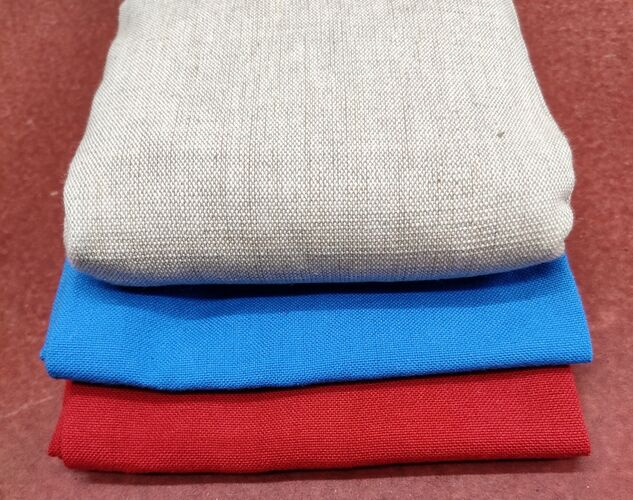 Three organic cotton heat pads are folded and stacked, red at the bottom, blue in the middle and linen coloured on top
