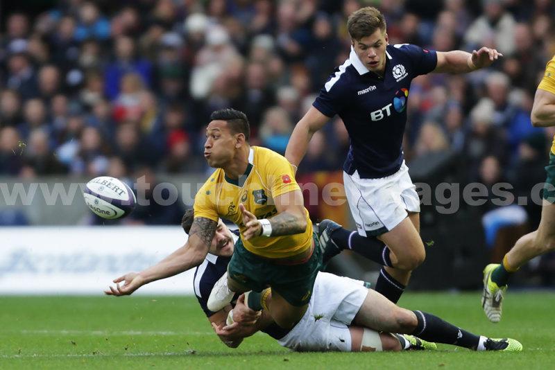 Israel Folau of Australia offloads despite tackle from Alex Dunbar of Scotland
