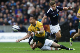Israel Folau of Australia offloads despite tackle from Alex Dunbar of Scotland