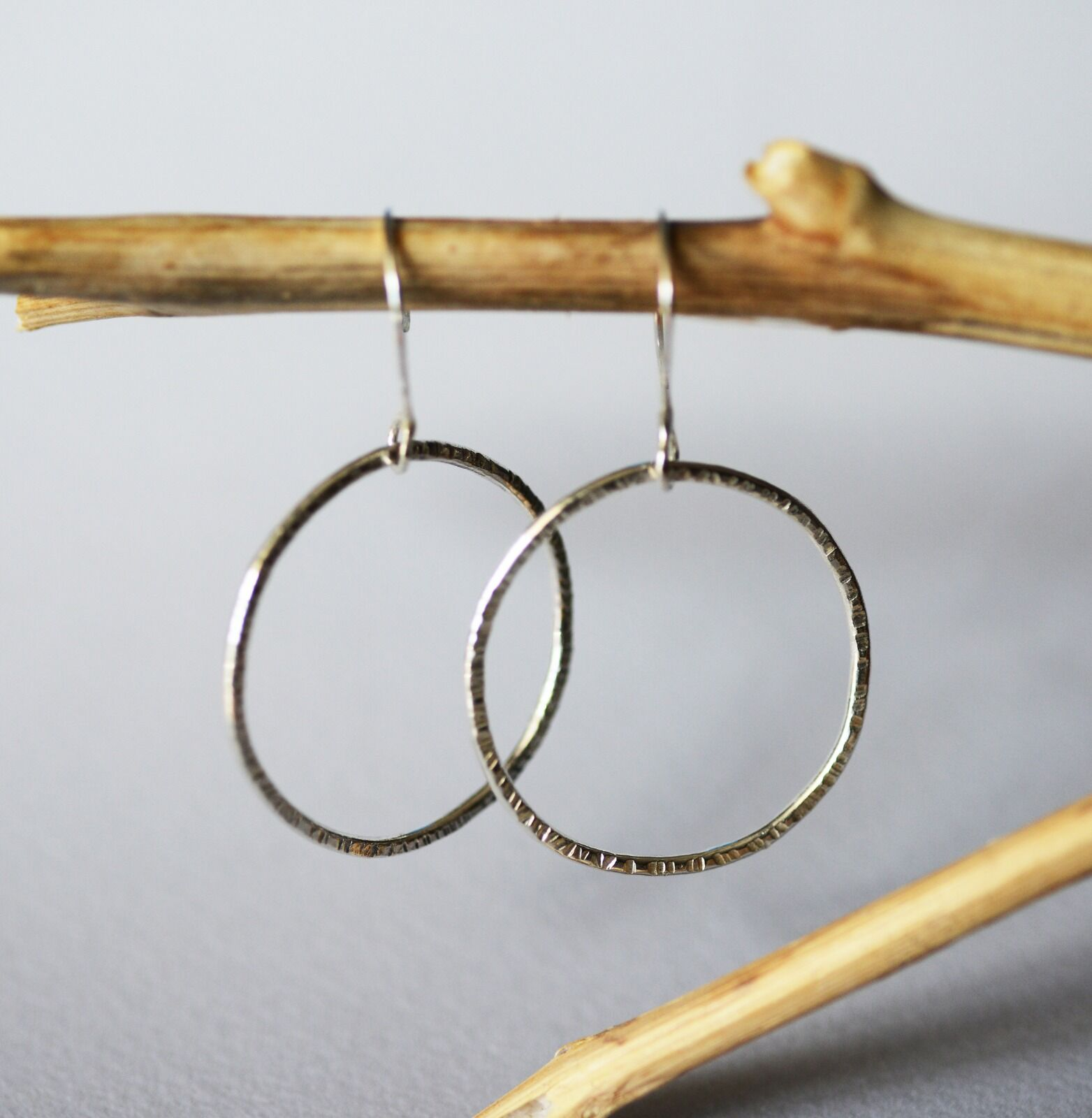 E18026 - Sterling silver hoop earring. Light hammered texture. French style ear wires