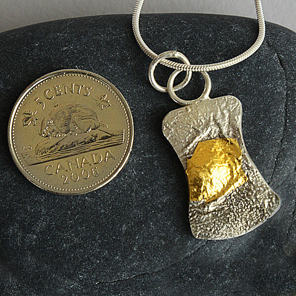 Small hour-glass shaped pendant. 24kt gold on reticulated silver,
