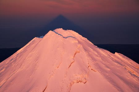 Alpenglow on Summit of Mt Taranaki / Mt Egmont at Dawn, and Shadow, Taranaki, North Island, New Zealand - aerial