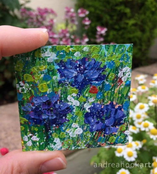 Mini wildflower painting of cornflowers held in the hand in garden