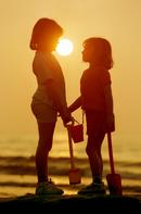 Two young girls enjoy the sunset at Borth near Aberystwyth, Mid Wales.