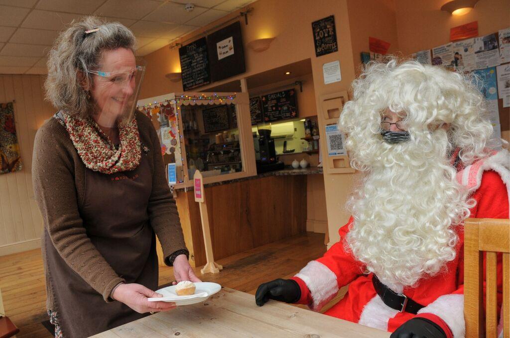 Becky serves Santa a mince pie at the Border Bean