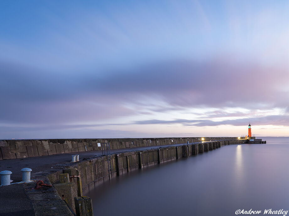 Harbour wall and lighthouse at sunrise, long exposure