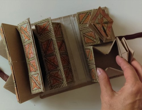 Square box open with recangular stack of boxes on left