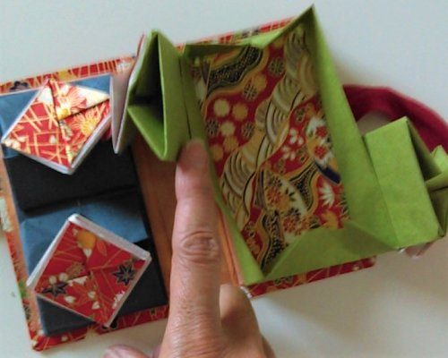 Rectancular box below square boxes open. Lined with patterned paper. Note that square boxes open on alternate sides.