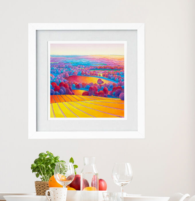 Colourful pen and wash landscape painting in a white frame. Stripy yellow and purple fields lead to more fields and purple/pink trees at sunset.
