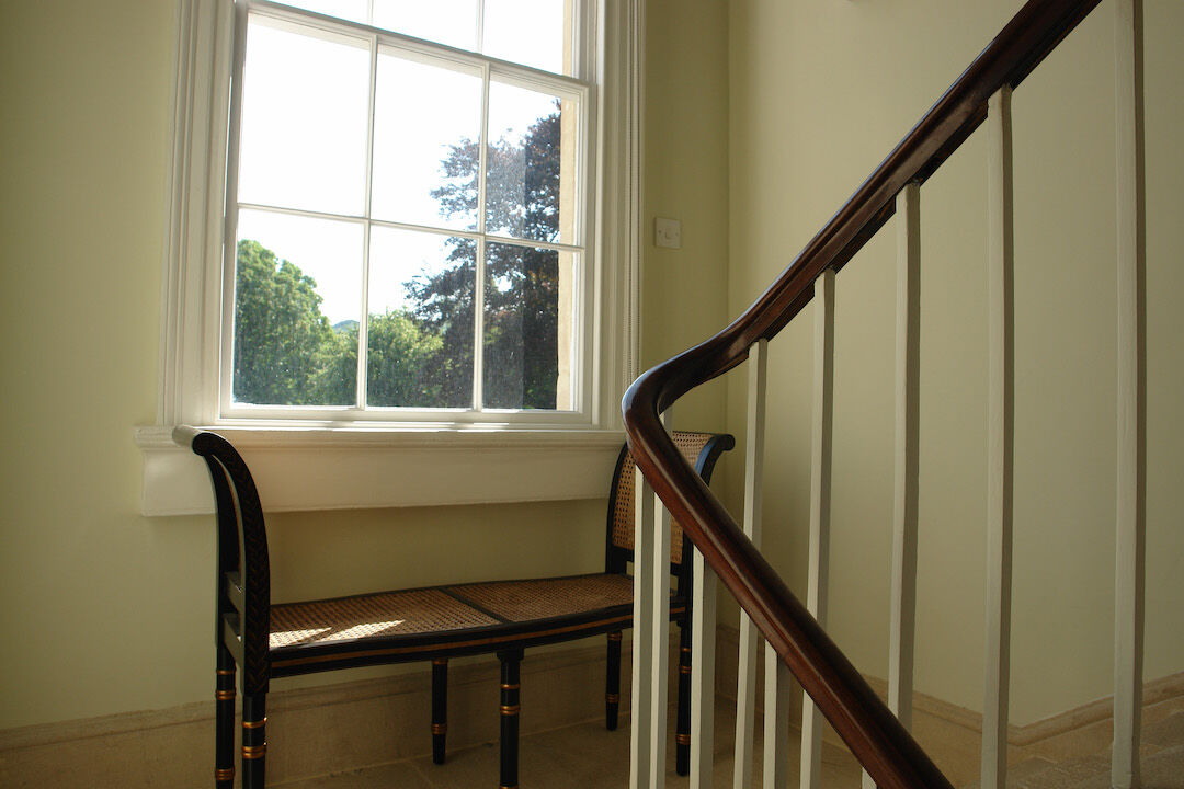 stairwell and bannisters and window in Bath with walls painted in Soft Angelica by Designers Guild