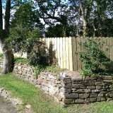 8m post & rail planed round top fence nestled behind low stone wall