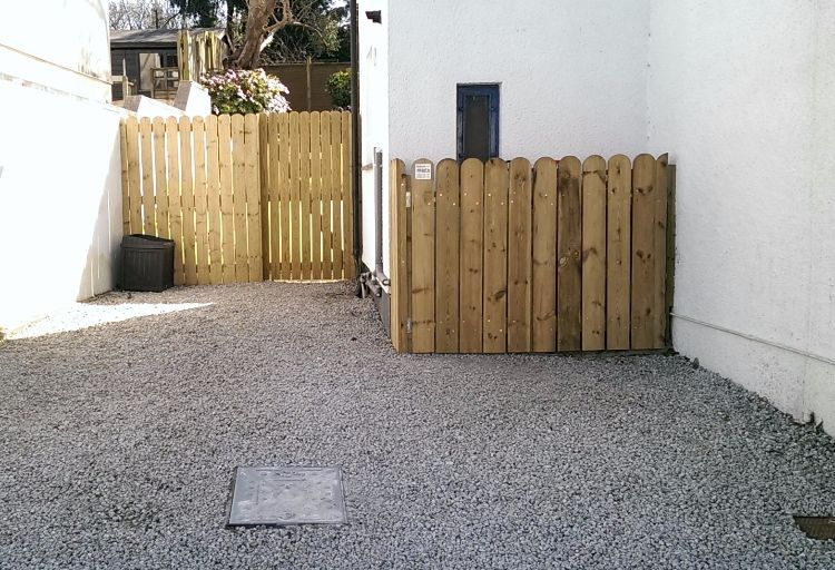 Planed round top timber gives this fence, gate & storage area a nice finish