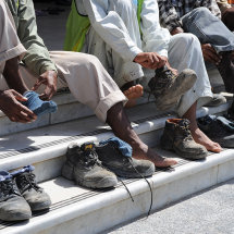 JP1 9824 Workers after prayer time put their shoes back on in unison