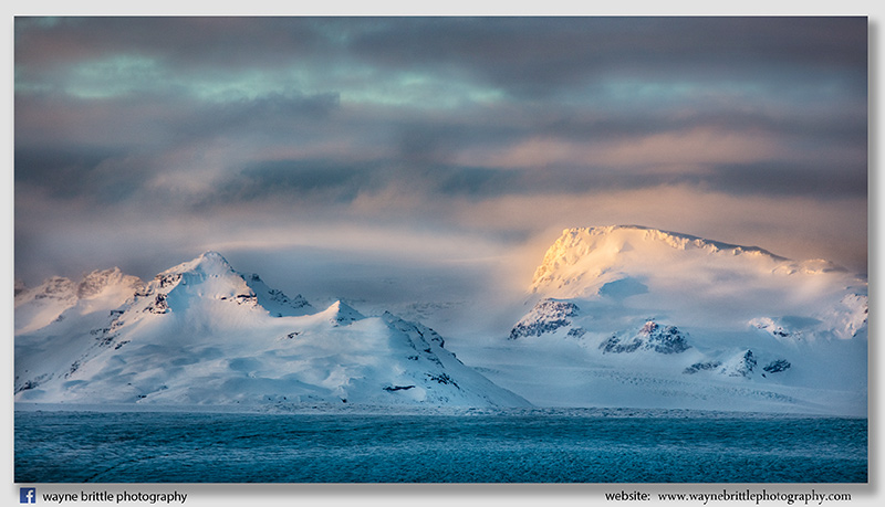 Light across the snow capped mountains