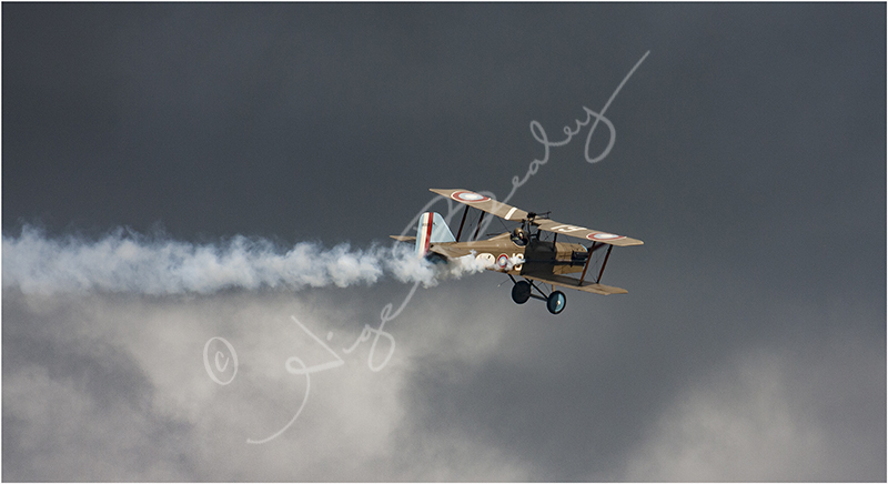 Smoking Bi Plane against a foreboding sky