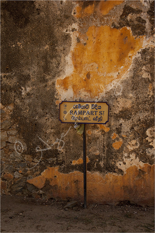 A street sign against a well weathered wall
