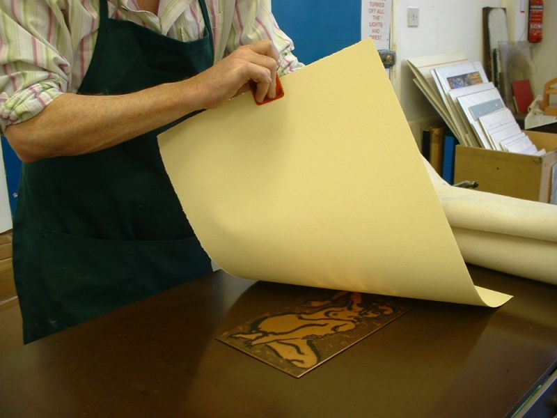 Covering the inked plate with damp paper