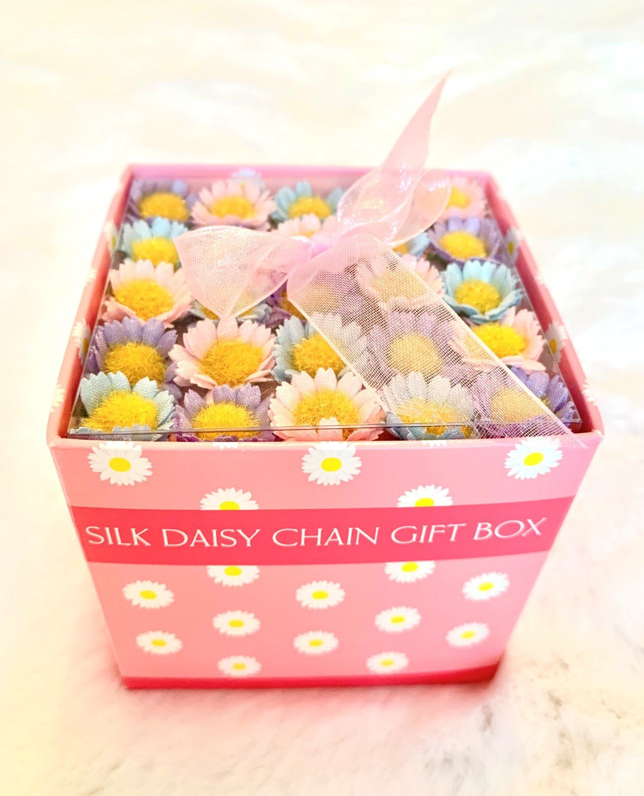 Box of 40 pastel coloured daisies, pink blue and purple.