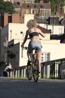 Blonde Girl on mountain bike pedalling over bridge
