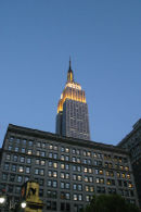 The Empire State Building in New York City, peeking over the top of another building.