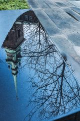 Spire, tree, water and stone slabs, London City, UK
