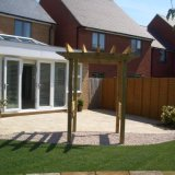 Modern arch with side slats leads from terrace to lawn