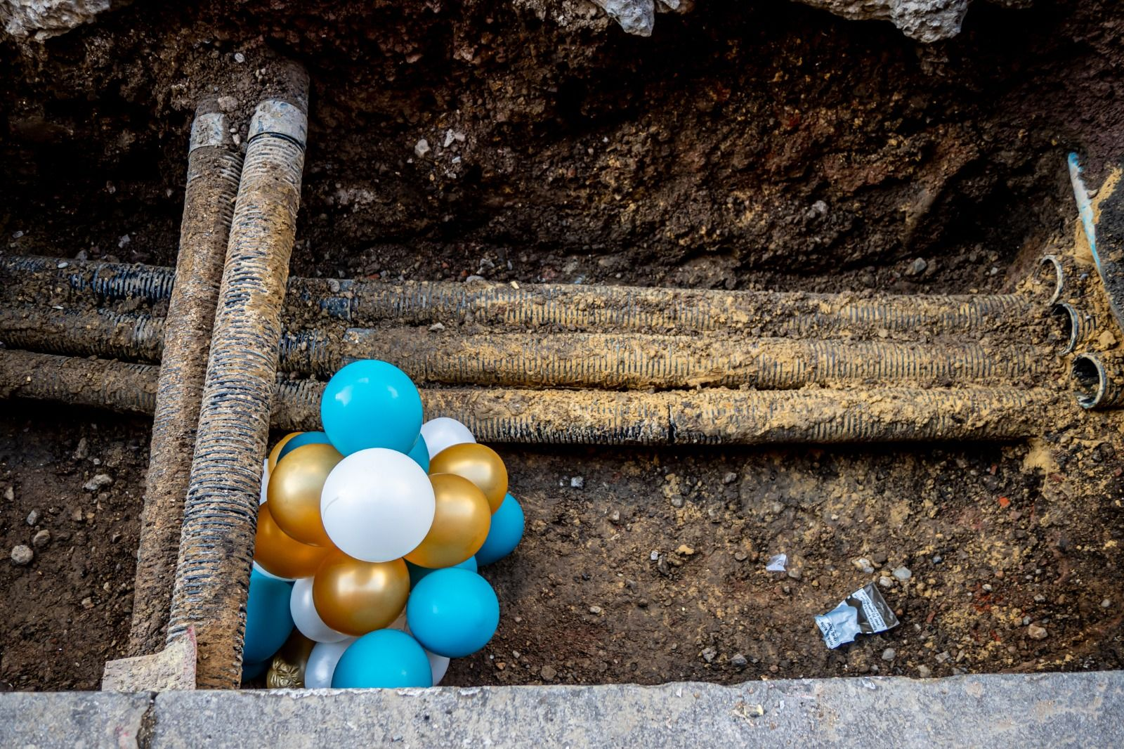 Candid street photography of colourful balloons in a dug trench, on a street in the West End of London.