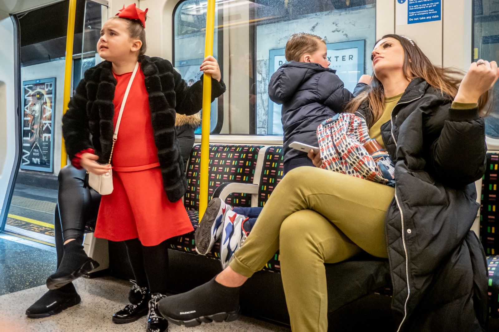 Candid street photography of a family on a London Underground train.