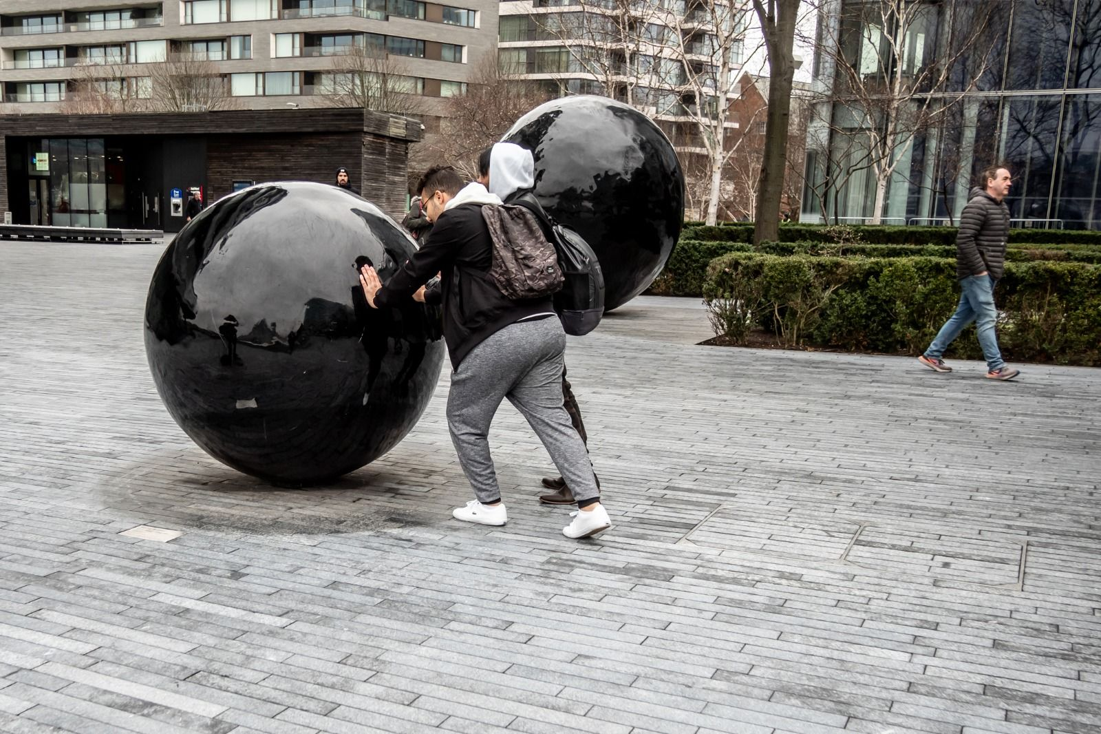 Street photography of a man pretending to push a large stone ball on Bankside, London.