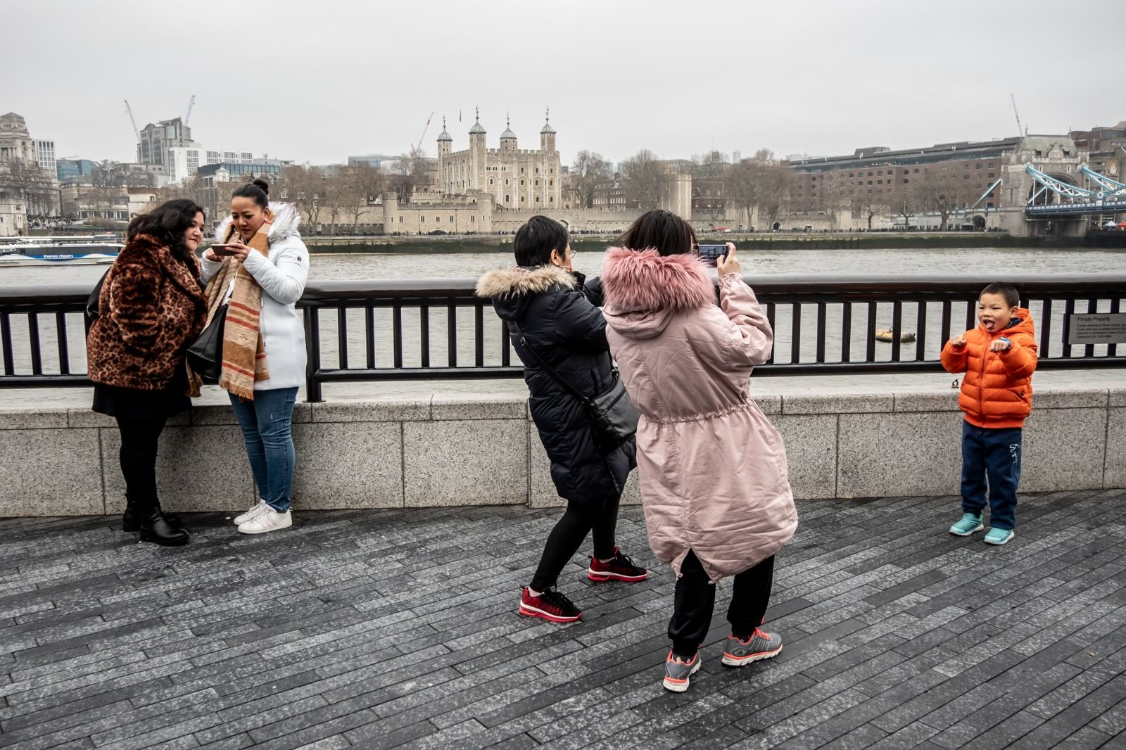Street photography of tourists taking a photo of a young boy, near Tower Bridge in London.