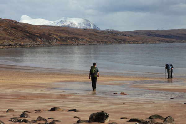 02D-1373 Walkers Beachcombing on the Beach at Red Point with the View Towards the Snow Covered Torridon Mountains Wester Ross West Coast of Scotland