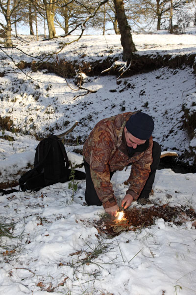 02D-9780 Using a Fire Steel and Birch Bark to Create Fire in a Woodland Environment in Winter Snow