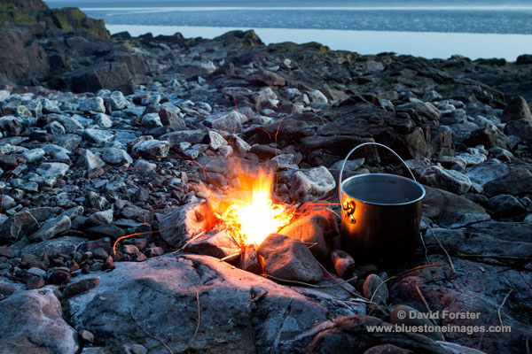 02M-3305a Fire with Cooking Pot on a Rocky Beach at Dusk