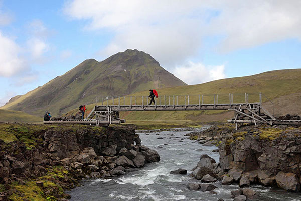 03D-5406 Hikers Crossing a Bridge Over the River Kaldaklofskvisl on the Laugavegur Hiking Trail With the Mountain of Storasula Behind Iceland
