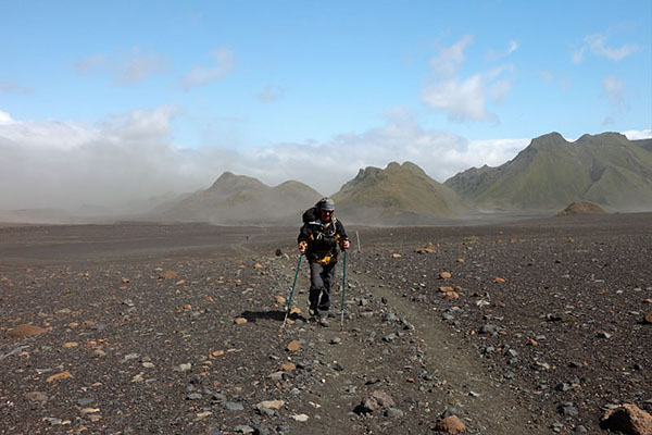 03D-5585 Hiker in the Emstrur Area on Day 3 of the Laugavegur Hiking Trail With Volcanic Dust Storm Behind Iceland