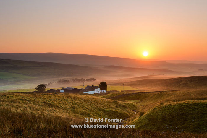 The North Pennine farm of Peghorn Lodge illuminated by the rising sun as mist rises in the valley below, Upper Teesdale, County Durham UK