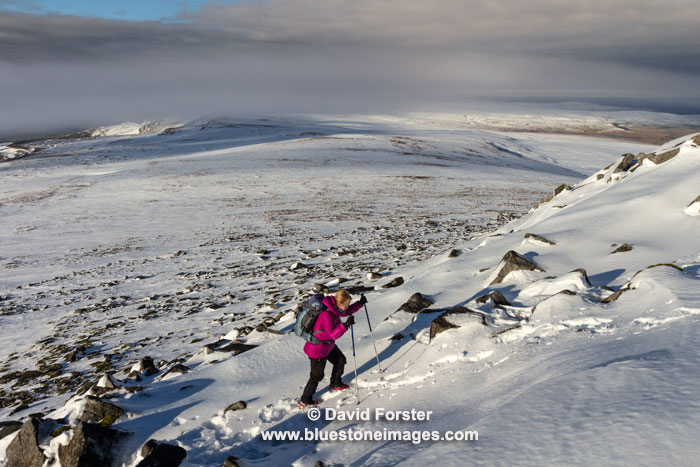 Walker Ascending Cross Fell in Winter with the Weather Phenomenon of the Helm Bar Forming in the Background, North Pennines, Cumbria, UK