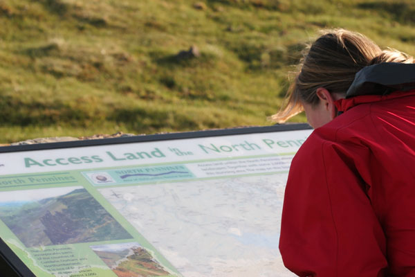 06-5128 Female Walker and Access Land Information Board, Cow Green Reservoir, Upper Teesdale, County Durham