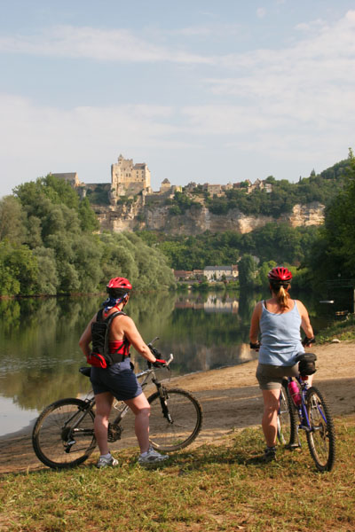 06-7562 Female Cyclist and View to Beynac-at-Cazenac, Dordogne Valley, France