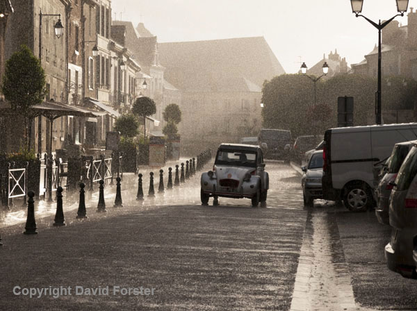 06D-8044 French Street Scene. Classic Citroen 2CV Driving Along a Street in the Pouring Rain in the Town of Ambroise Indre et Loire France